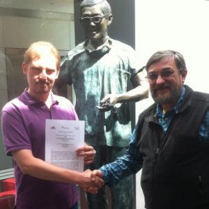 Prof. Martinac (rechts) und Prof. Friedrich mit dem Vertrag vor der Statue von Dr. Victor Chang, dem verstorbenen gründer und Namensgeber des Instituts.