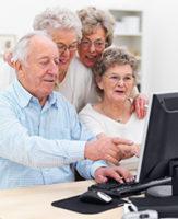 Vier Senioren sitzen vor einem Computer