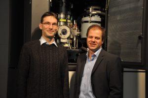 Dr. Benjamin Butz und Prof. Erdmann Spiecker vor dem aberrationskorrigierten Titan³ 80-300, das sie für die mikroskopische Untersuchung der Versetzungen in Bilagen-Graphen einsetzten. (Bild: FAU)