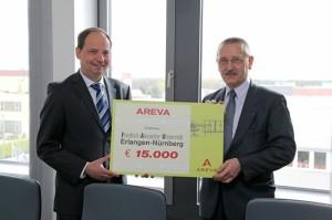 AREVA-Standortleiter Wolfgang Däuwel überreichte den Spendenscheck an FAU-Kanzler Thomas A.H. Schöck. (Bild: FAU/Georg Pöhlein)