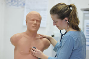Student Merle Winkelmann practices listening to the chest. A realistic-sounding heartbeat can be heard from inside the model. (Image: Universitätsklinikum Erlangen)