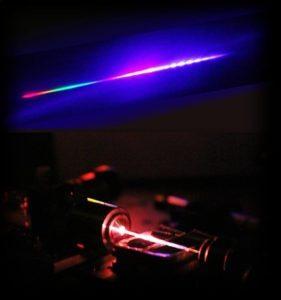 Licht mit hohem UV-Anteil: Die Strahlung, die aus der photonischen Kristallfaser austritt, fächern die Erlanger Forscher mit einem Prisma auf ähnliche Weise auf, wie Wassertropfen Sonnenlicht zu einem Regenbogen brechen. Dabei erhalten sie ein Spektrum (oberer Teil des Bildes), das den sehr breiten ultravioletten Anteil der Strahlung zeigt (rechter Teil des Spektrums). Die normalerweise unsichtbare UV-Strahlung wird durch die Photolumineszenz, die durch das energiereiche UV-Licht induziert wird, sichtbar. An den sichtbaren Bereich (linker Teil des Spektrums) schließt sich der unsichtbare, sehr große infrarote Abschnitt des Spektrums an. (Bild: Xin Jiang)