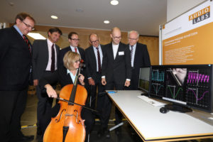 Watching one of AudioLabs' exciting research projects in action: sensors can not only detect the pitch of the cello subjectively but determine it exactly. From left to right: Dr. Bernhard Grill, Acting Director of IIS; Prof. Dr. Joachim Hornegger, FAU President; Dr. Florian Janik, mayor of the city of Erlangen; Prof. Dr. Albert Heuberger, AudioLabs speaker and Director of Fraunhofer IIS; Fabian-Robert Stöter, research assistant at AudioLabs; Prof. Dr. Alexander Kurz, Executive Vice President Human Resources, Legal Affairs and IP Management at Fraunhofer-Gesellschaft; Dr. Sybille Reichert, FAU Chancellor. Image: Fraunhofer IIS/Kurt Fuchs.