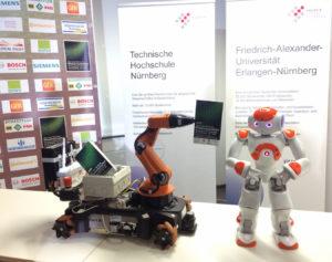 """Auch der kleine humanoide Roboter """"Nao"""" (rechts) begleitet die Besucher durch den Abend: Im Nürnberger Bionicum demonstriert er, wie gut er sich selbst bei Nacht zurechtfindet. (Bild: FAU/Susanne Langer)"""