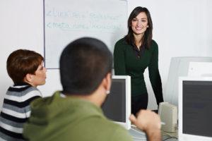 Eine Frau steht vor einem Whiteboard, zwei Personen schauen sie an und sitzen vor Computerbildschirmen