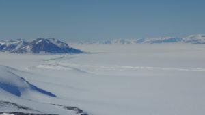 Blick auf das George-IV Ice Shelf, welches zwischen Alexander Island (Vordergrund) und der westl. Antarktischen Halbinsel (Hintergrund) eingespannt ist. Der markante Spaltenbogen markiert die Aufsetzlinie, den Übergang zwischen Zuflussgletscher und schwimmendem Schelfeis. Aufgenommen während eines NASA IceBridge Messfluges am 16. November 2011. Photo: Matthias Braun.