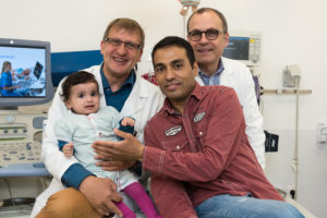Prof. Dr. Sven Dittrich (back left) and Prof. Dr. Robert Cesnjevar (back right) treated and operated on the little girl after she was admitted to hospital with a severe heart defect. Raghad's father is incredibly grateful for the life-saving support she received in Erlangen. (Image: Universitätsklinikum Erlangen)