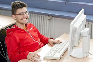 Mathe-, Physik- und Informatik-Student Kevin Höllring sitzt an einem Tisch mit Computerbildschirm und Tastatur