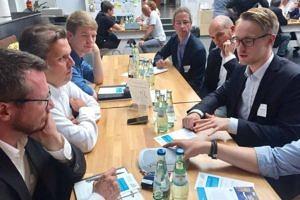 Thorge Harm sitzt mit Vertretern der Volkswagen AG an einem Tisch