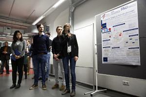 Eine Gruppe von Menschen betachtet ein Plakat, Studierende präsentieren