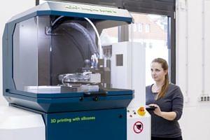 Hannah Riedle steht vor einem 3D Drucker