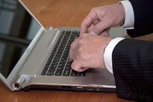 Hände tippen auf einer Laptoptastatur