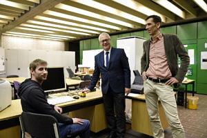 Drei Personen stehen und sitzen vor einem Arbeitsplatz mit Computer