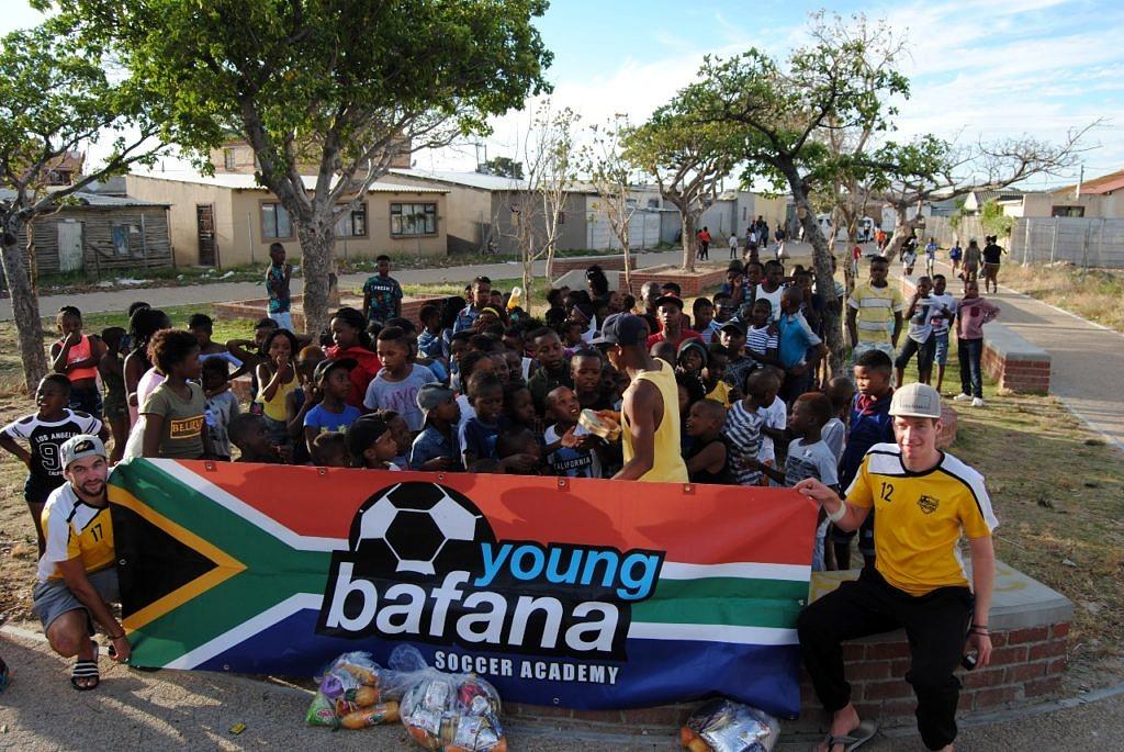 """Ehrenamtliche Helfer sind mit den Kindern auf einem Platz versammelt und halten ein Roll-up mit der Aufschrift """"Young Bafana Soccer Academy""""."""