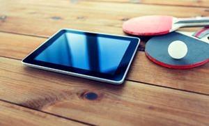 Ein Tablet, zwei Tischtennisschläger und ein Tischtennisball liegen auf einem Holzuntergrund