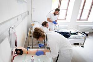 Eine Studentin nimmt an einem künstlichen Arm Blut ab; im Hintergrund behandelt ein Student den Simulationspatienten.