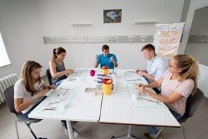 Vier Studierende und ein Tutor sitzen an einem Tisch und nähen etwas.