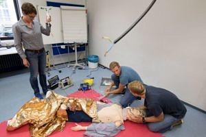 Zwei Studierende knien am Boden und versorgen eine Simulationspuppe. Eine Frau hält den Infusionsbehälter.