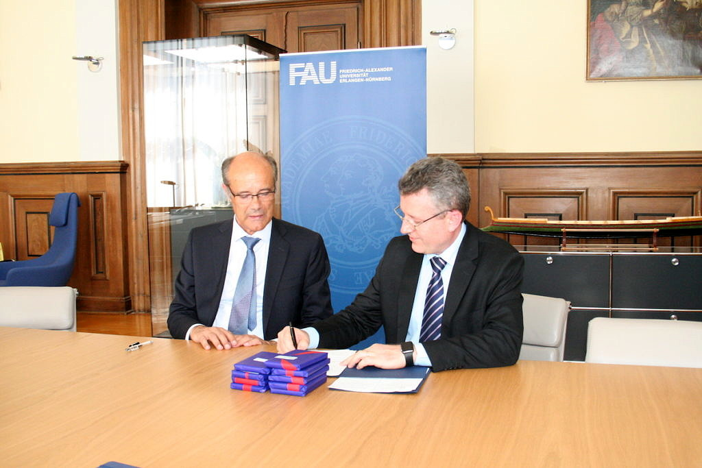Prof. Dr. Günter Leugering and Odir Antônio Dellagostin sign the contract.
