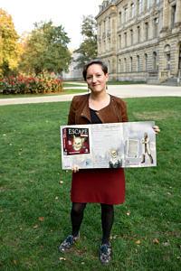 FAU-Mitarbeiterin hält im Schlossgarten eine Broschüre zum neuesten Spiel in der Hand.