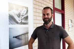 Portraitfoto: Künstler vor seinen Fotos