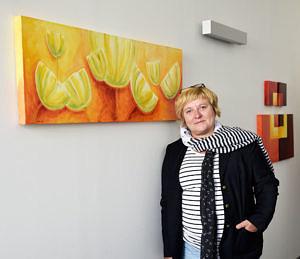 Portraitfoto: Künstlerin ist an Wand gelehnt; im Hintergrund hängen ihre Bilder