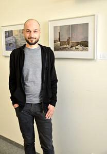 Künstler steht an der Wand vor einem seiner Bilder