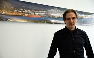 Künstler in seinem Büro; an der Wand hängt eine Collage aus Panoramafotos