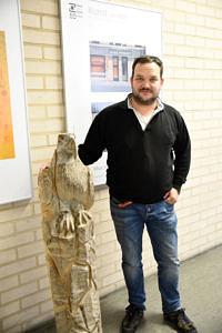 Portraitfoto des Künstlers; ein Holzfigur (Adler) ist mit abgebildet