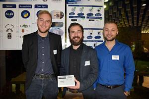 Gruppenbild der drei Studenten, die ein digitales Türschild zeigen.