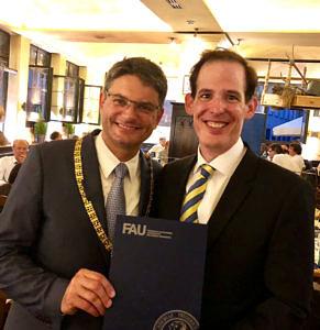 Gemeinsames Bild mit Prof. Dr. Joachim Hornegger (links) und Dr. Paul Gumminger (rechts): Prof. Dr. Joachim Hornegger zeigt eine blaue Umschlagsmappe mit FAU-Logo.