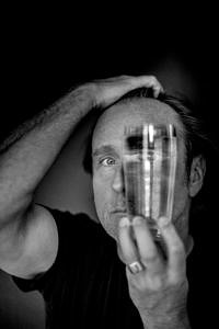 Schwarz-weiß-Foto von Bjarne Mädel: Es ist nur die linke Gesichtshälfte zu sehen, da er sich vor die rechte ein Wasserglaß hält.