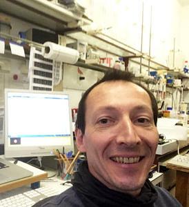 Selfie von Christian Emilius: Im Hintergrund sieht man seinen PC und ein paar Arbeitmaterialien eines Labors.