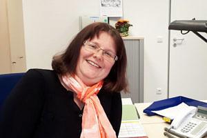 Martina Büttner sitzt an ihrem Arbeitsplatz und blickt fröhlich in die Kamera.