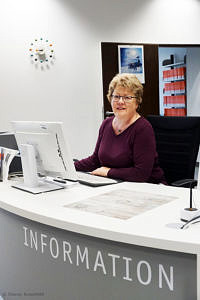 Veronika Rummler sitzt an einer Informationstheke vor einem Computer und lächelt in die Kamera..