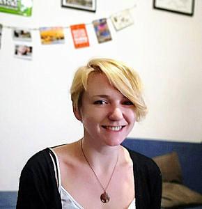 Portraitbild von Theresia Wolf: Im Hntergrund hängen Postkarten an der Wand.