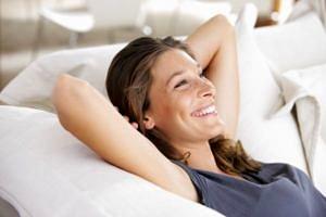 Frau sitzt glücklich auf Sofa