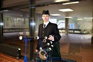 Portraitbild eines Mitarbeiters in Schottenrock, Dudelsackoutfit und mit Dudelsack