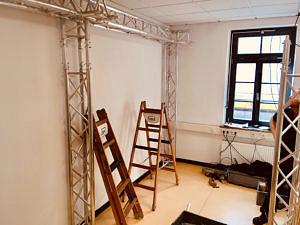 Blick in einen noch leeren Raum: Eine Metallkonstruktion ist befestigt und es stehen Leitern rum.
