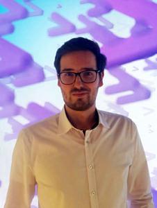Portraitbild eines ehemaligen Teilnehmers des Patenschaftsprogramms, der vor einem lila leuchtenden Hintergrund steht.