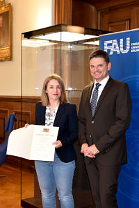 Portraitbild mit Mitarbeiterin (links) und Uni-Präsident: Stolz präsentiert sie ihre Urkunde