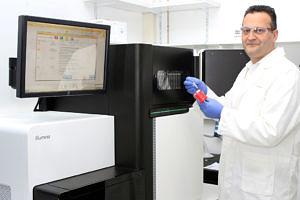 Wissenschaftler steht im weißen Doktorkittel vor einem Computer: Mit einer Zange hält er kleine Aufbewahrungsbehälter.