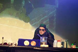 Professor im schwarzen Umhang und mit Kappe und Brille als Zauberer verkleidet. Vor ihm Reagenzgläßer und chemische Substanzen: Das Scheinwerferlicht ist auf ihn gerichtet.