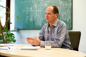 Bild von Professor wie er an einem Tisch sitzt und zu einem Publikum spricht. Im Hintergrund: eine beschriebene Tafel