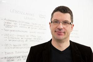 """Portraitbild des Professors: Im Hintergrund ein weißes Board auf dem etwas zum Thema """"digitales Lernen"""" geschrieben steht."""