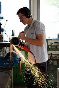 Student fräßt in der Werkstatt und die Funken sprühen dabei.