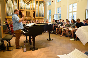 Image from rehearsal: Students look at their songbooks while the choirmaster conducts.