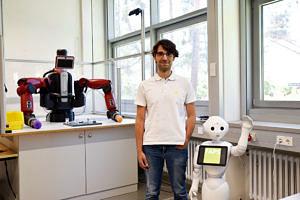 Rechts des Mitarbeiters ist ein Roboter mit Gesicht zu sehen, der winkt; links des Mitarbeiters ist ein maschinenartiger Roboter mit zwei Greifarmen zu sehen.