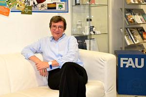 Portraitbild von Kathrin Möslein: Sie sitzt auf einer Couch. Im Hintergrund ist eine Wand mit vielen Postkarten, eine Glaßvitrine und einem blauen FAU-Sitzwürfel zu sehen.