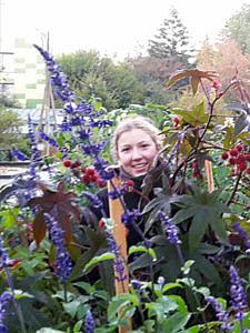 Das Gesicht einer Frau ragt zwischen Blättern und lilafarbenen Blumen hervor.
